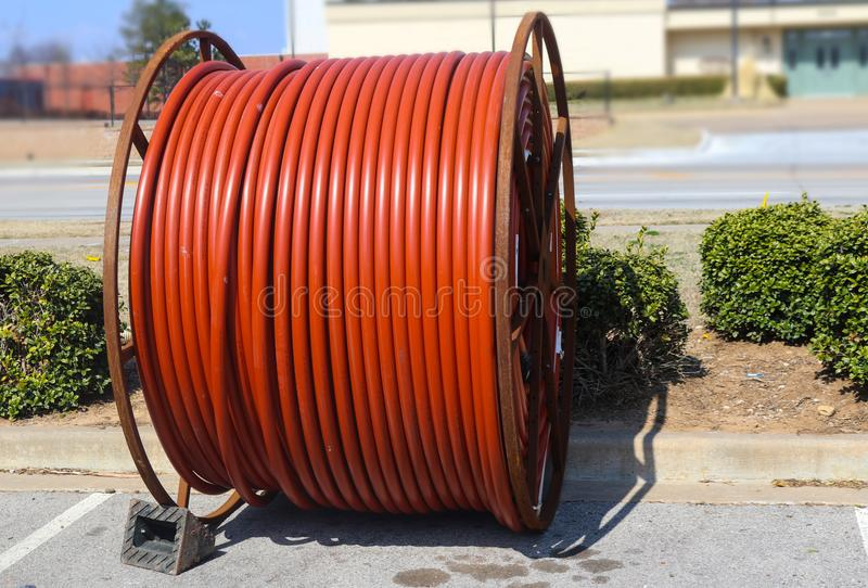 Huge roll of orange cable for underground cable installation sitting along a street stock photography