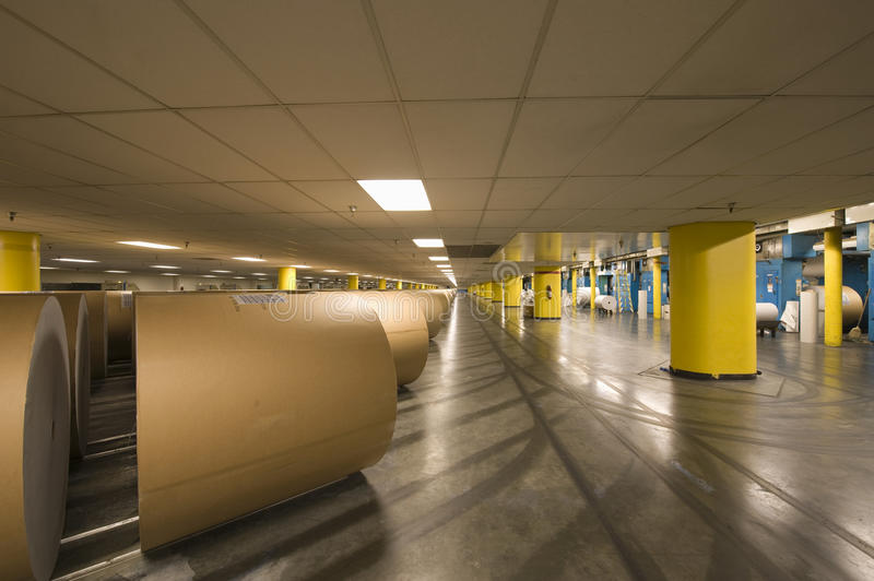 Huge Rolls Of Paper In Newspaper Factory. View of huge rolls of paper in spacious newspaper factory royalty free stock image