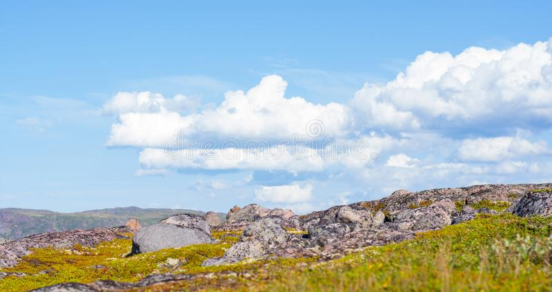 Huge rounded stones on backdrop of hills, small mountains and low Northern the sky. stock photos