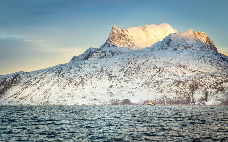 Huge Sermitsiaq mountain covered in snow with blue sea and small fishing boat, nearby Nuuk city, Greenland royalty free stock photos
