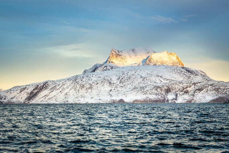 Huge Sermitsiaq mountain covered in snow with sea in the foreground, nearby Nuuk city, Greenland royalty free stock photos