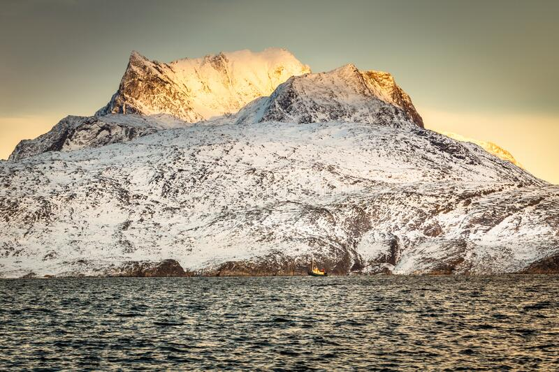 Huge Sermitsiaq mountain in a sunset rays covered in snow with blue sea and small fishing boat, nearby Nuuk city, Greenland stock photos