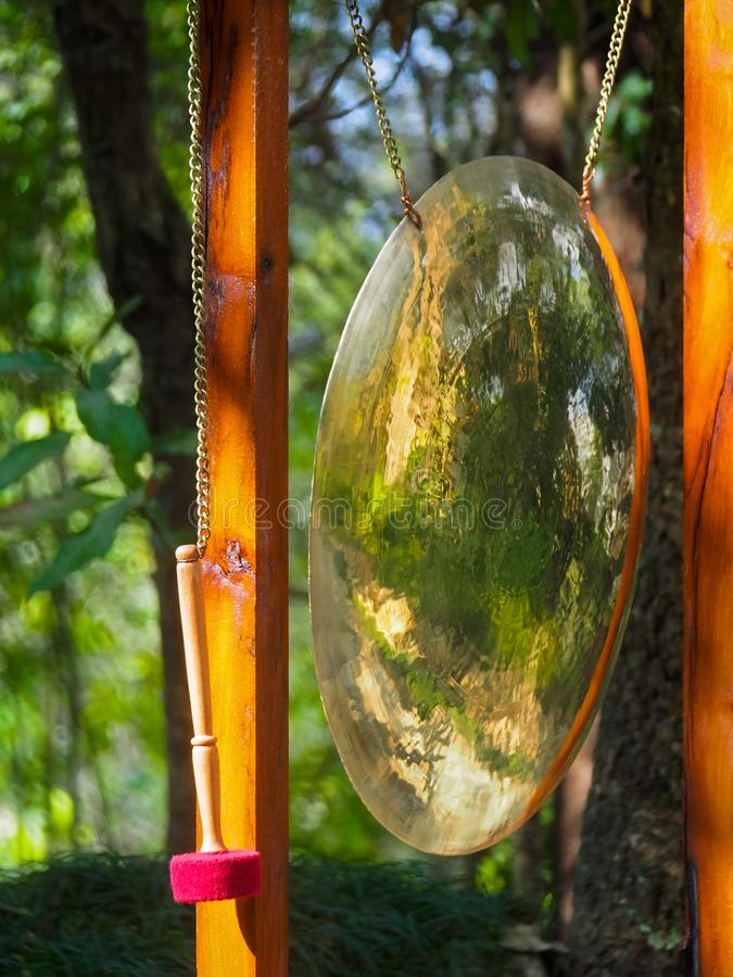 Huge shiny Buddhist gong hanging in frame next to mallet in Nepal stock images