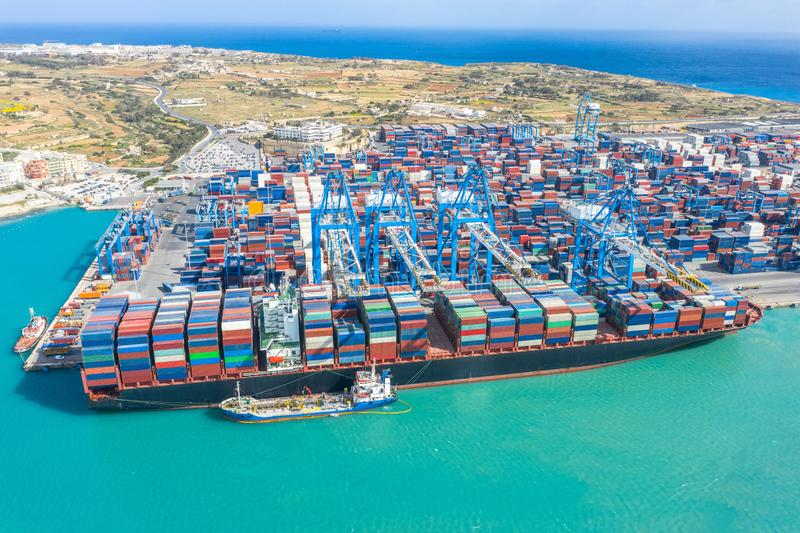 Huge ship with a large number of containers, moored to the port, cranes unload cargo. Great port, maritime transport, maritime. Traffic delivery concept royalty free stock photos