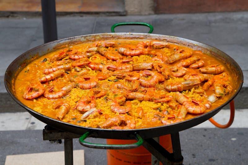 Huge shrimp paella in cooking pan stock image