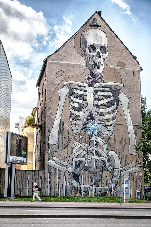 Huge skeleton graffiti on the house in Koln Germany. Huge skeleton graffiti on the house in Koln (Germany) with old lady walking by stock photography