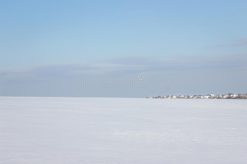 Huge snow covered field leading to the village under the blue sky royalty free stock photo