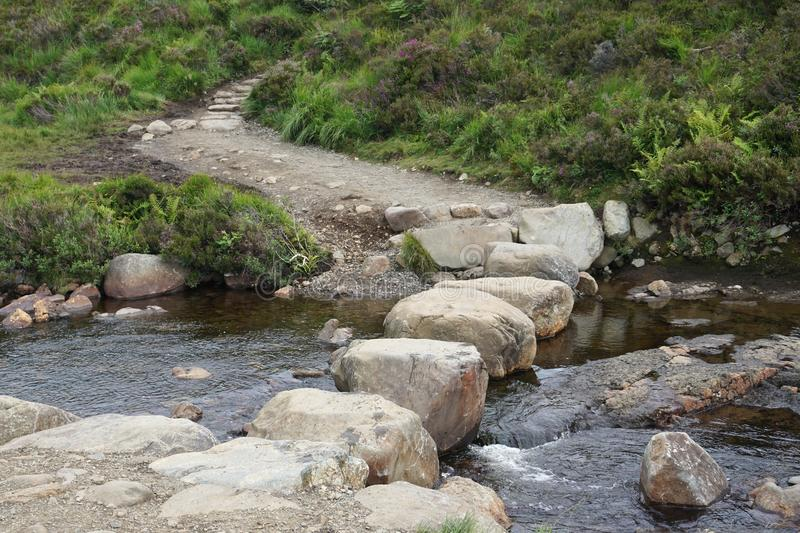 Huge stepping stones across a flowing stream near the Fairy Pools on the Isle of Skye. Boulders make a convenient bridge across the river stock photography