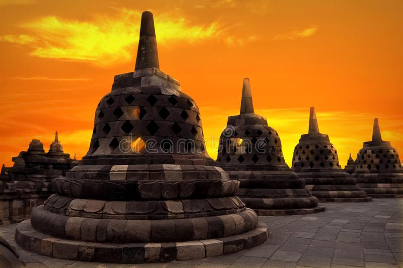 Huge stone Buddhist stupas against the background of a beautiful orange sunrise in the Borobudur Temple. Indonesia. Java island. stock images
