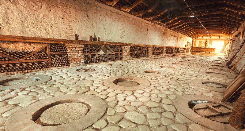 Huge stone cellar with aged wine bottles and qvevri, large earthenware vessels under ground. Rural storage of winery. stock photography