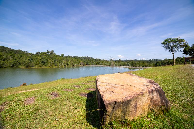 Huge stone on green field and river stock photography