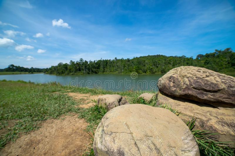 Huge stone on green field and river royalty free stock photo
