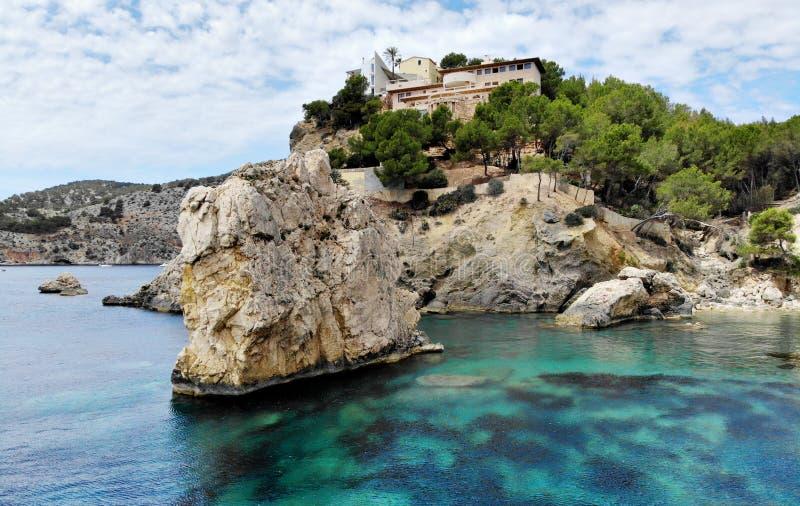 Huge stones rcky coast of Cala en Cranc of Mallorca. Picturesque nature turquoise Mediterranean waters bay, hillside house luxury summer villa, cloudy sky stock photos