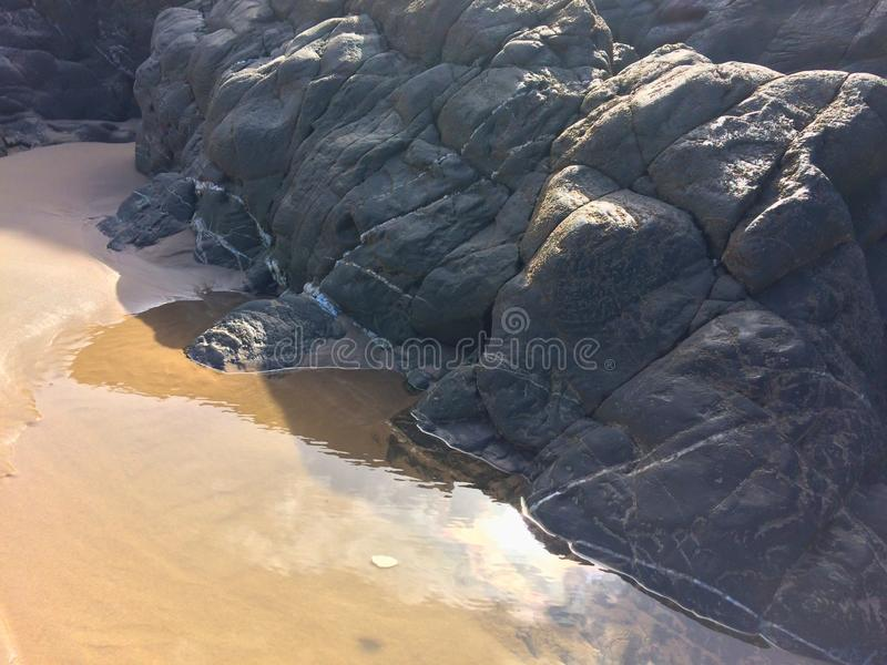 Huge stones on the sandy shore. Rocks and sand royalty free stock photos