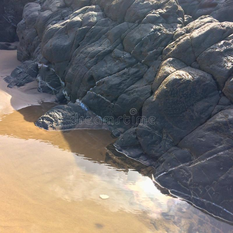 Huge stones on the sandy shore. Rocks and sand royalty free stock photography