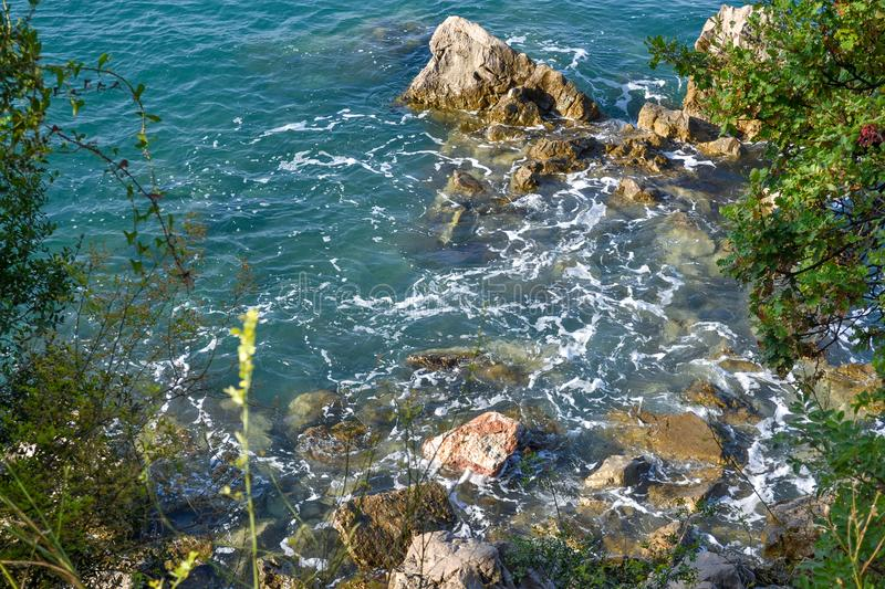 Huge stones in the sea and waves. On a sunny day. View from above. Montenegro. The Budva Riviera.  stock photos