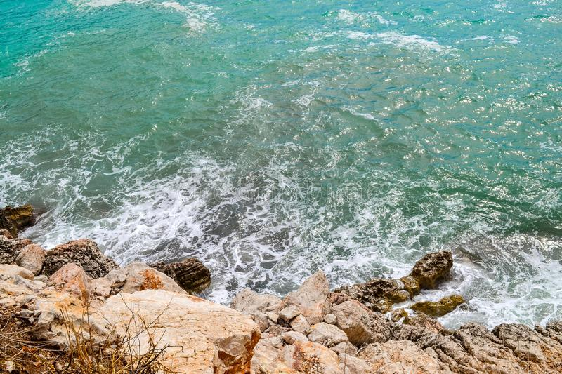 Huge stones in the sea and waves. On a sunny day. View from above. Montenegro. The Budva Riviera.  stock photography