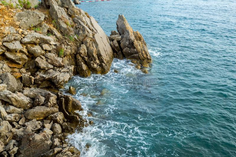 Huge stones in the sea and waves. On a sunny day. View from above. Montenegro. The Budva Riviera.  stock photo