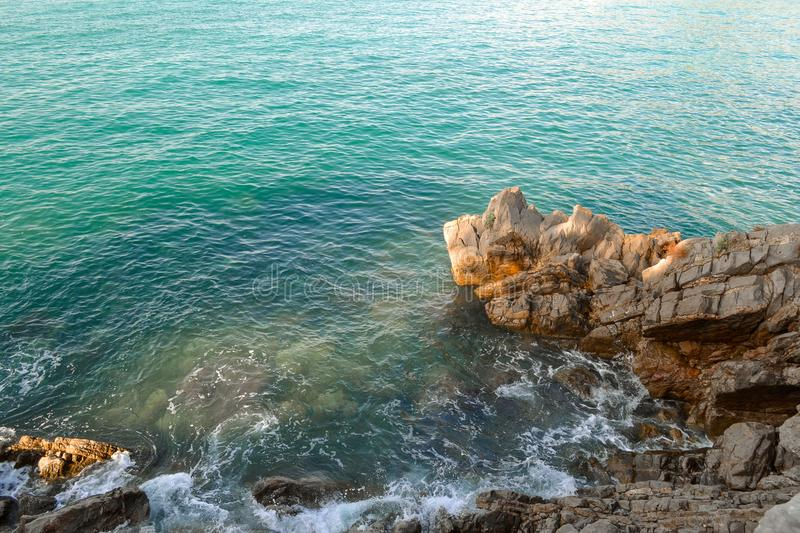 Huge stones in the sea and waves. On a sunny day. View from above. Montenegro. The Budva Riviera.  royalty free stock image