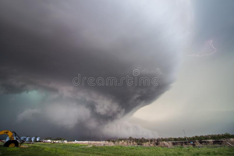 A huge supercell storm with a ground scraping wall cloud and lightning bolt stock photography