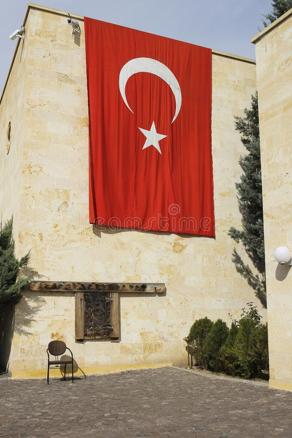 Huge Turkish flag hanging from the roof of cream colored building. Vertical photo of huge Turkish flag hanging from the roof of cream colored building with old stock image