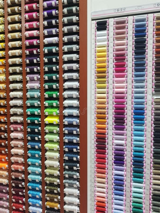 A huge wall, collection full of cotton reels, lots of colorful horizontal spools of thread on display at the notions store stock image