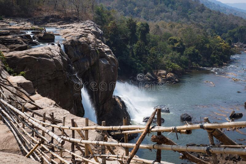 A huge waterfall Athirapally in Kerala, India. White streams of water of the waterfall break into small splashes and flow in a strong stream, Indian tourists stock photography