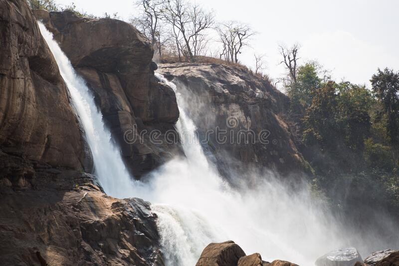 A huge waterfall Athirapally in Kerala, India. White streams of water of the waterfall break into small splashes and flow in a strong stream, Indian tourists stock image