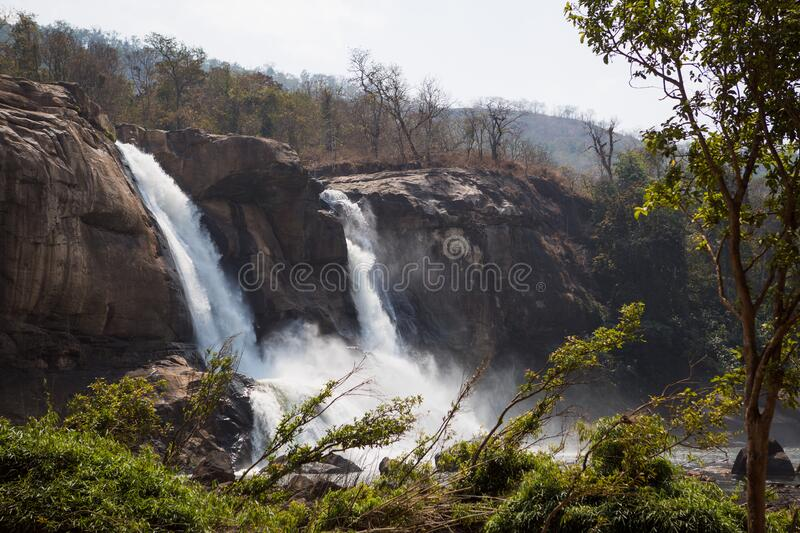 A huge waterfall Athirapally in Kerala, India. White streams of water of the waterfall break into small splashes and flow in a strong stream, Indian tourists royalty free stock photography