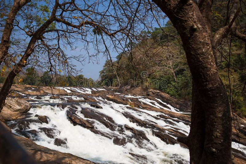 A huge waterfall Athirapally in Kerala, India. White streams of water of the waterfall break into small splashes and flow in a strong stream, Indian tourists royalty free stock images