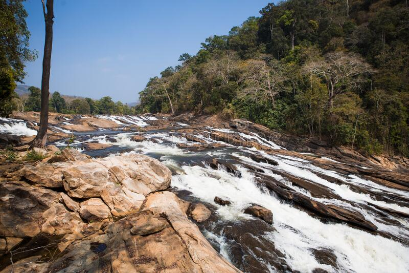 A huge waterfall Athirapally in Kerala, India. White streams of water of the waterfall break into small splashes and flow in a strong stream, Indian tourists royalty free stock photo