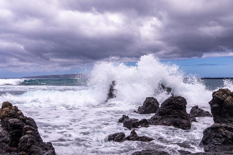 Huge wave splashes on a rocky beach. A large lava rock completely covered in a white ocean spray, La Perouse bay, Maui,, Hawaii royalty free stock images