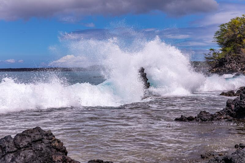 Huge wave splashes on a rocky beach. A large lava rock completely covered in a white ocean spray, La Perouse bay, Maui,, Hawaii stock photo
