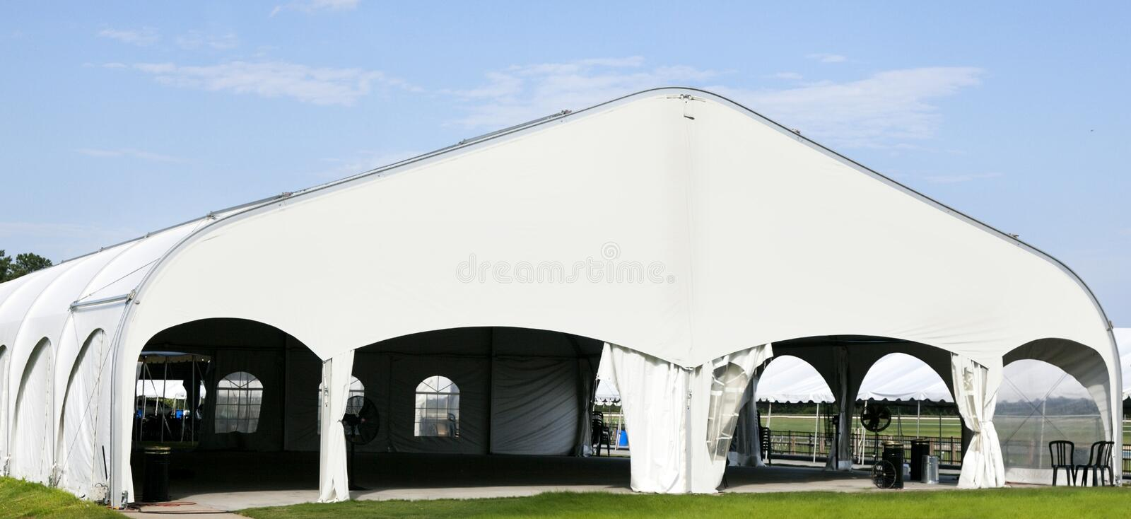 Huge White Event Tent. Tent event tent. Empty. Nobody. Horizontal. Brick and stone patio in foreground. Horizontal stock photography