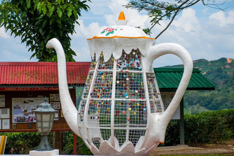 Huge white metal kettle. Colorful padlocks heart shaped on blurred background, symbol of love. Sabah, Borneo, Malaysia. Huge white metal kettle. Colorful stock photography