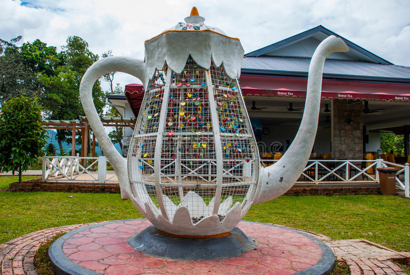 Huge white metal kettle. Colorful padlocks heart shaped on blurred background, symbol of love. Sabah, Borneo, Malaysia. Huge white metal kettle. Colorful stock image
