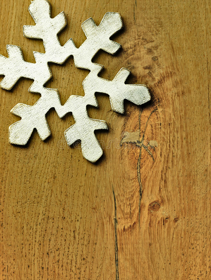 Huge white snowflake and wooden background. stock image