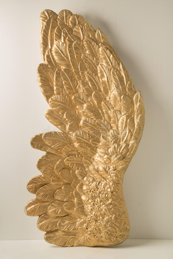 Huge wing with golden feathers royalty free stock photos