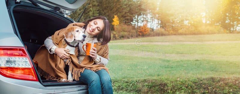 Huges de femme son chien avec des châles se reposant ensemble dans le tronc de voiture image libre de droits