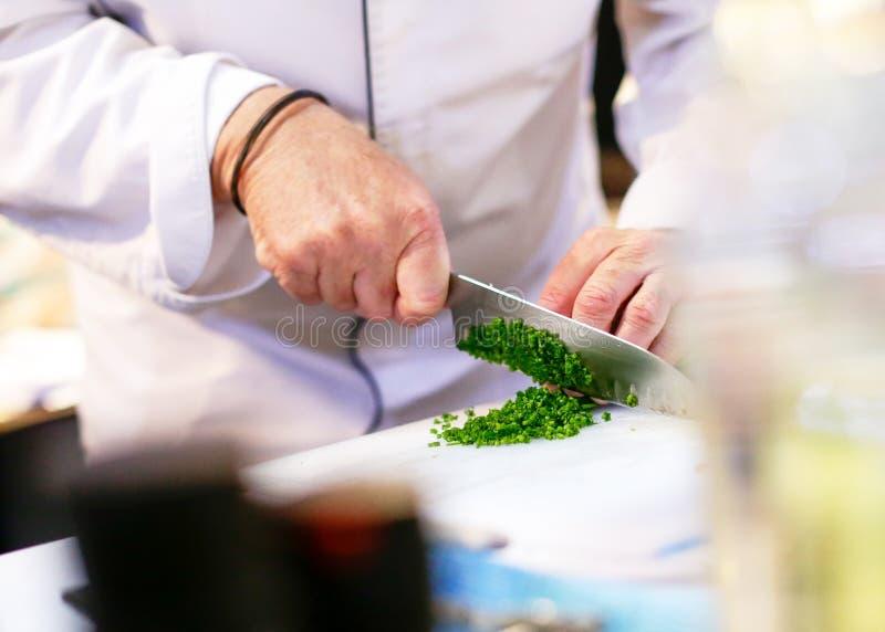 Hugga av salladslöken, kock som klipper nya grönsaker för att laga mat arkivfoton