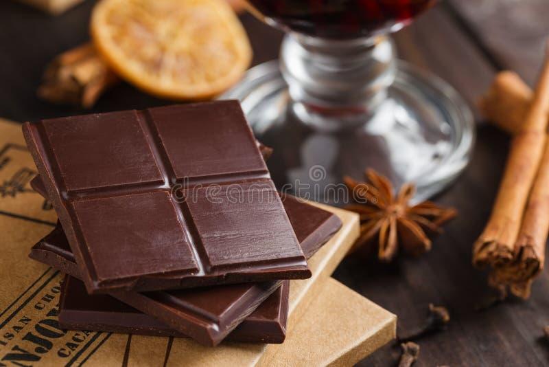 Huggen av bitter choklad med exponeringsglas av funderade vin och kryddor royaltyfri bild