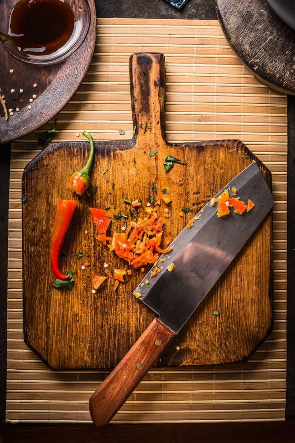 Huggen av chilipeppar med kniven på träskärbrädan, bästa sikt varm mat Kryddor för smakligt göra till kok fotografering för bildbyråer