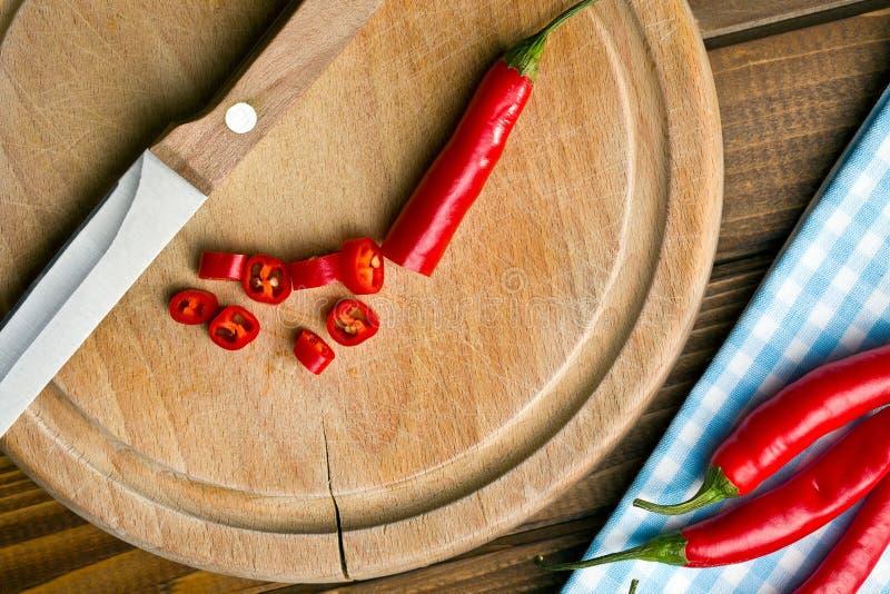 Huggen av chilipeppar på skärbräda royaltyfri fotografi