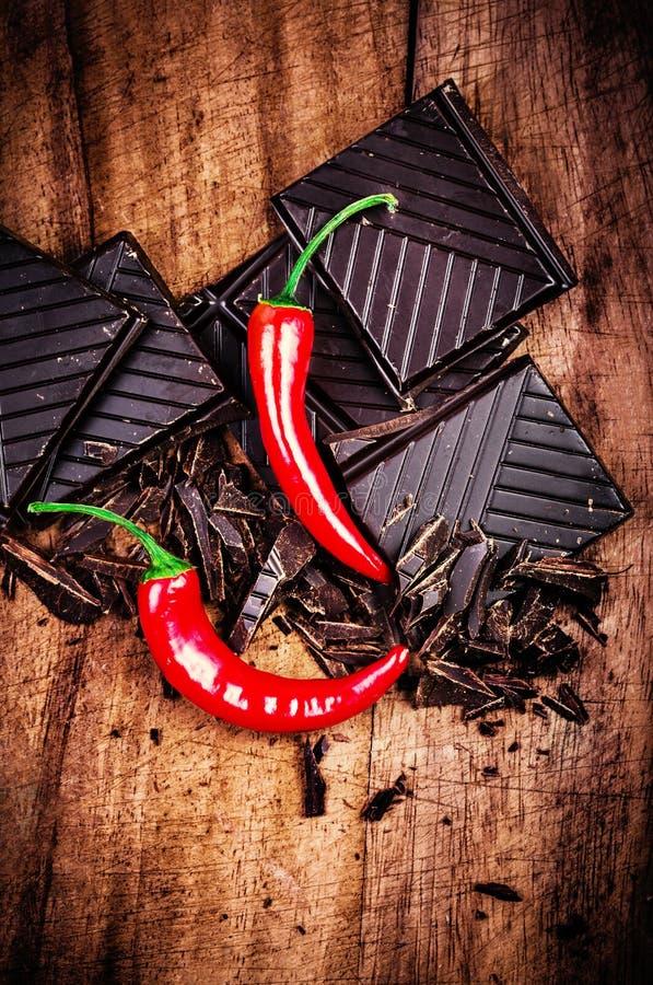 Huggen av chokladstång med peppar för röd chili på träbackgroun royaltyfria foton