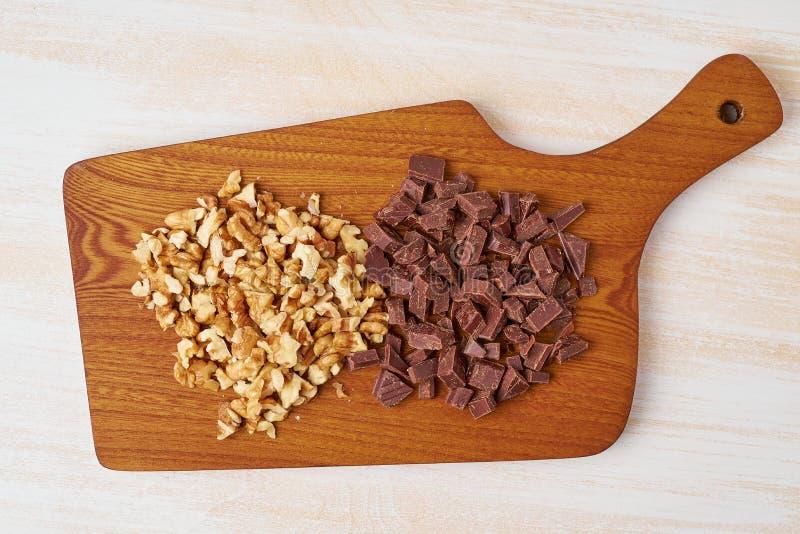 Huggen av valnötter och choklad på träbräde E royaltyfri foto