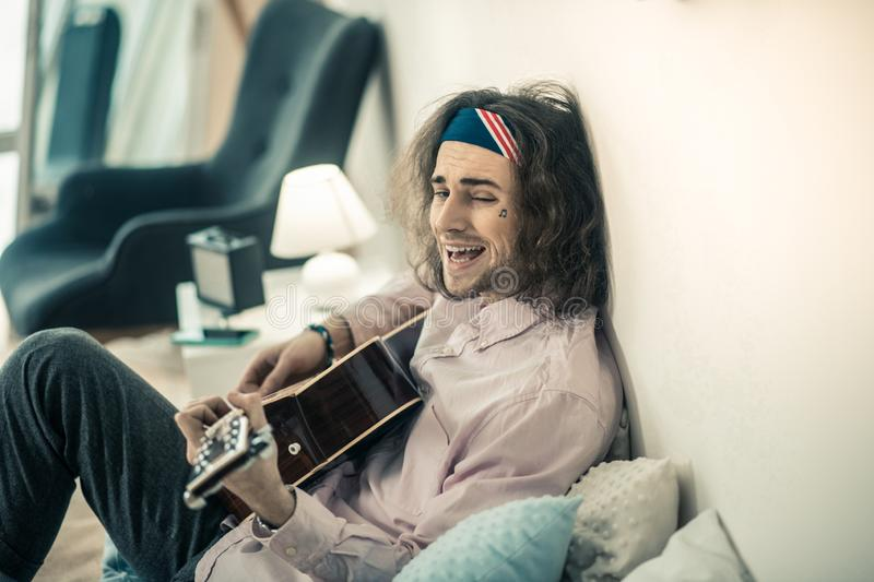 Weird bearded young musician making faces while resting on the bed royalty free stock photo