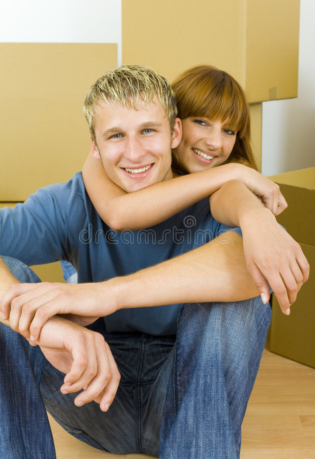 Hugging couple. Young couple sitting on the floor in flat. They're looking happy. Woman is hugging man. They're looking at camera. Front view stock images