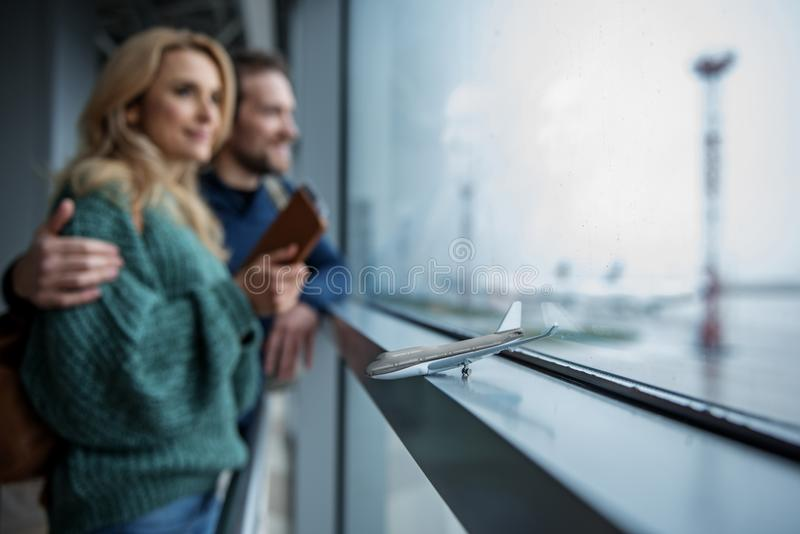 Little airplane standing on window near people stock photo