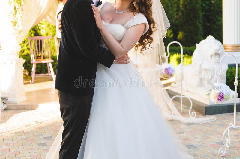Hugging Couple. Bride and groom hugging at restaurant's yard royalty free stock images