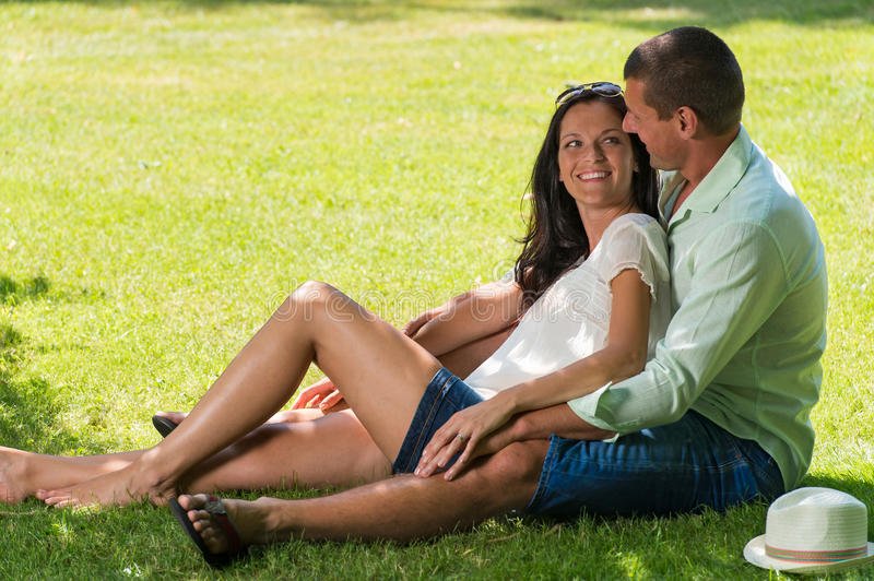 Hugging couple sitting in grass outdoors royalty free stock photos